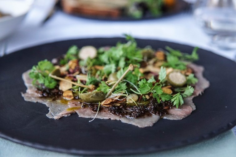 treat your loved one to an award-winning meal at a Michelin starred restaurant this Valentine's Day, here carpaccio of beef is topped with nuts, herbs and vegetables.