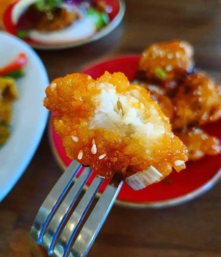 A Kambuja's delicious spicy cauliflower bite on a fork, covered in sesame seeds and spring onions.