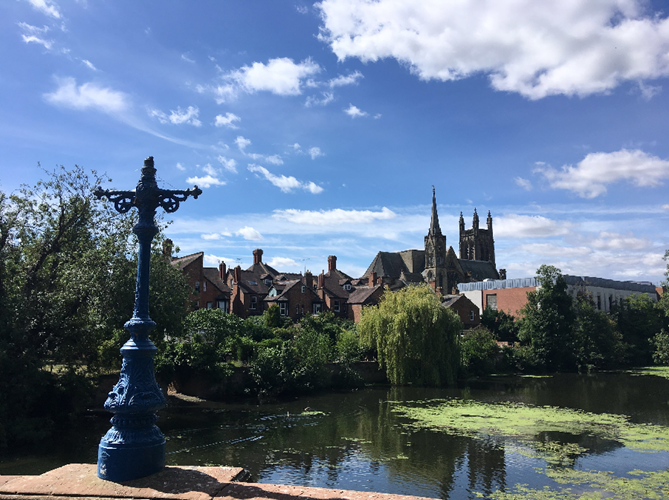 The town of Royal Leamington Spa sits behind a calm river in the sunshine.