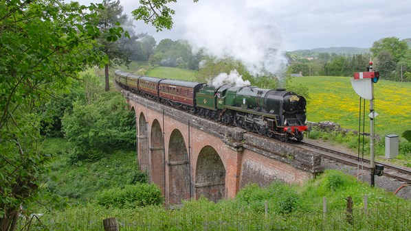 A steam locomotive crossing a brick bridge, while traveling through the English countryside.