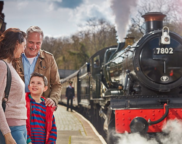 Family of 3 ready to board a steam locomotive